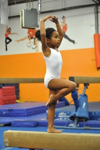 Girl in pirouette form on balance beam